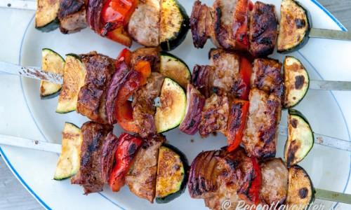 Varva fläskfilébitarna med rödlök, zucchini och paprika - fina färger och det håller köttet saftigt när du grillar det.