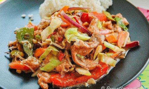 Wok med fläskkött och grönsaker på tallrik