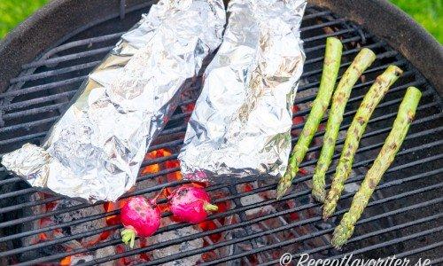 Foliepaketen grillas på utegrill tillsammans med lite grönsaker som sparris och rädisor.