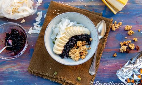 Kallrörd frögröt i tallrik med banan, granola, blåbär och kokos.