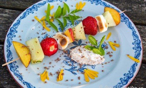 Fruktspett med jordgubbar och marshmallows på tallrik