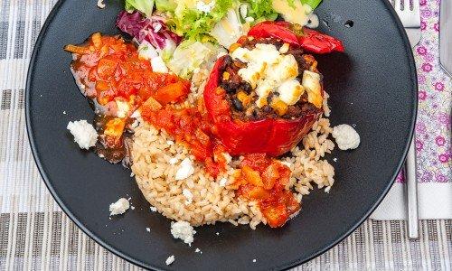Fylld paprika med tacofärs, fetaost, tomatsås, råris och sallad på tallrik.