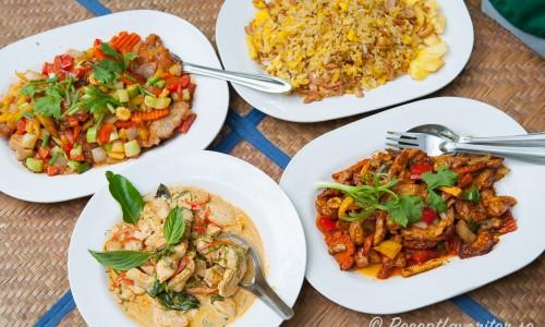 Thaikyckling med cashewnötter serverad med tre andra thairätter