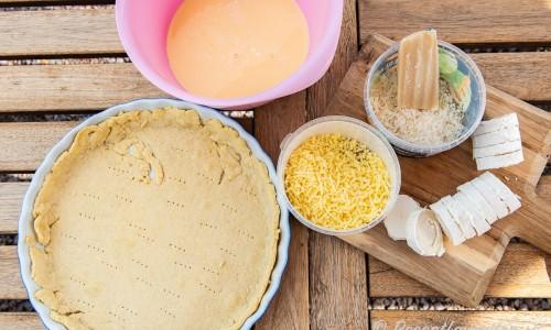 Ingredienser till Quiche Lorraine - äggstanning, förgräddat pajskal, getost i rulle, riven chevrette och lagrad ost.