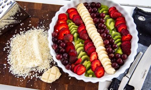 Bär och frukt till ginon lagd i mönster i en ugnssäker form med riven vit choklad bredvid.
