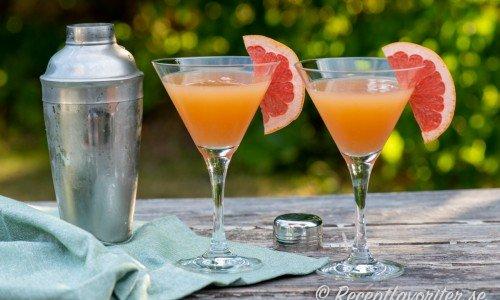 Grapefruktcocktail i glas garnerad med skivad grapefrukt.
