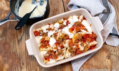De förkokta pastasnäckorna varvas i en ugnsform med fyllning, tomatsås, Bechamelsås och ost.