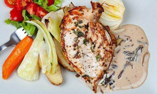 Grillad eller stekt kycklingfilé på tallrik med tillbehör