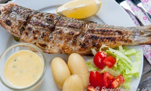 Grillad hel fisk med gräslökshollandaise och tillbehör på tallrik