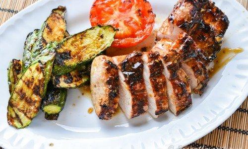 Grillad helstekt fläskytterfilé skivad till servering med grillad tomat och zucchini.