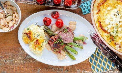 Grillad lammrostbiff serverad med tillbehör - här potatisgratäng med fetaost, marinerade stora vita bönor, grillad sparris och tomater.