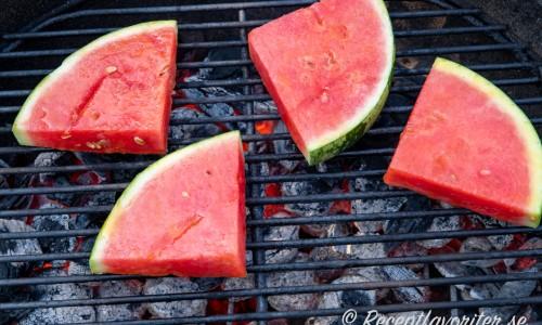 Bitar av vattenmelon med skalet kvar som grillas på utegrill