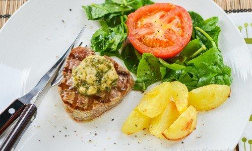 Grillad oxfilé med örtsmör, klyftpotatis, grillad tomat och grönsallad.