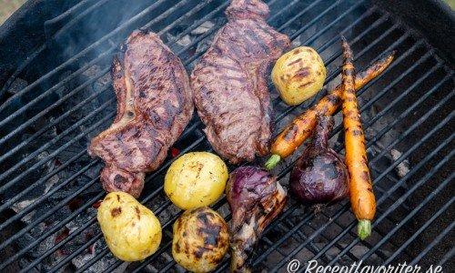 Ryggbiffen på grillen med grönsakstillbehör som potatis, knippmorötter och rödlök.