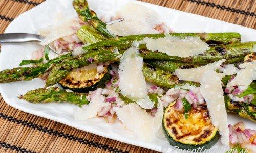 Grillad grön sparris och zucchinskivor toppade med vinägrett och hyvlad parmesan är ett gott grönsakstillbehör från grillen som passar till det mesta - speciellt fest och buffé