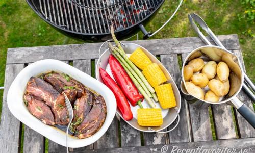 Ingredienser redo för grillen: vildsvinskarrén i marinad; ett fat grönsaker och kokt potatis.