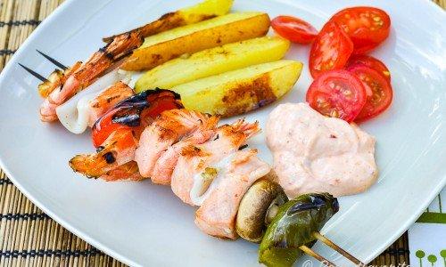 Grillspett med fisk och tillbehör på tallrik.