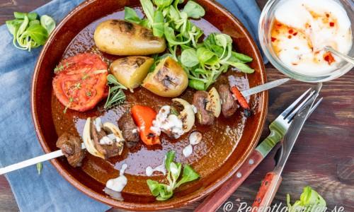 Grillspett med förslag på tillbehör som grillad potatis, tomat, sallad och en kall yoghurtsås med Sweet Chili.