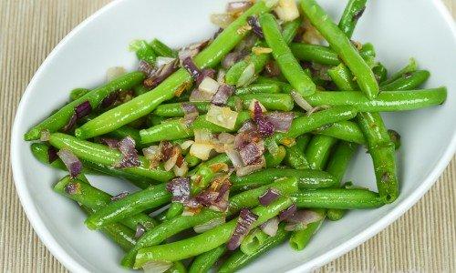 Gröna bönor som får god smak av vitlök, rödlök och olivolja