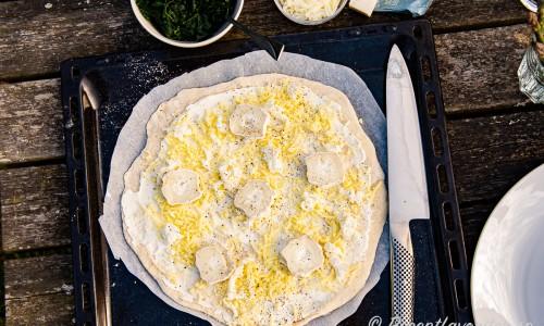 Pizzabotten förbereds med ett lager crème fraiche, riven mozzarella, smulad färsk mozzarella samt chèvre.