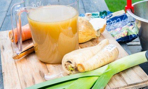 Grönsaksbuljong i kanna och ingredienser på skärbräda