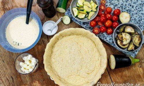Pajskalet innan det gräddas omgivet av ingredienser till pajen fetaost, äggstanning med ost och grädde, salt, peppar, zucchini, tomat och aubergine.