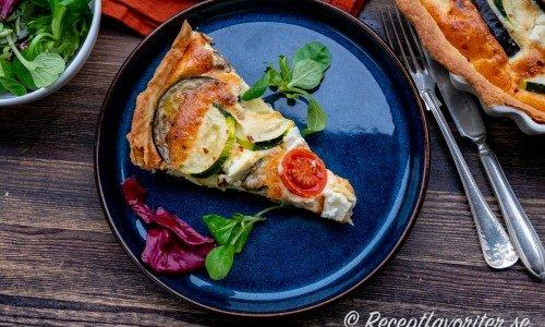 En bit grönsakspaj serverad med grönsallad på tallrik.