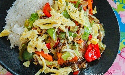 Grönsakswok på tallrik med ris