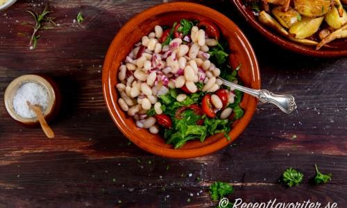 Grönsallad i skål med vit bönor och tomat