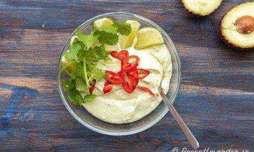 Guacamole garnerad med röd chilipeppar, färsk koriander och lime.