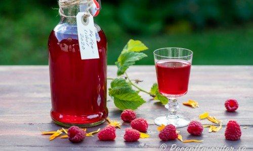 Hallonlikör på färska hallon i flaska och serverad i glas