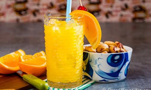 Harvey Wallbanger i glas med apelsinklyfta och jordnötter.