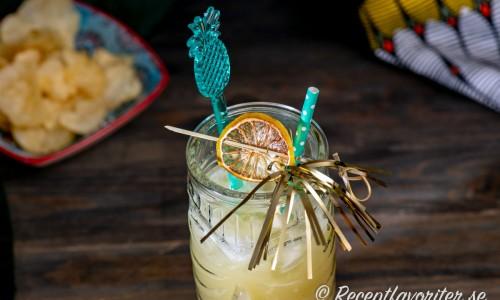 Garnering till Havana Beach drink med drinkpinne, sugrör och en skiva torkad lime.