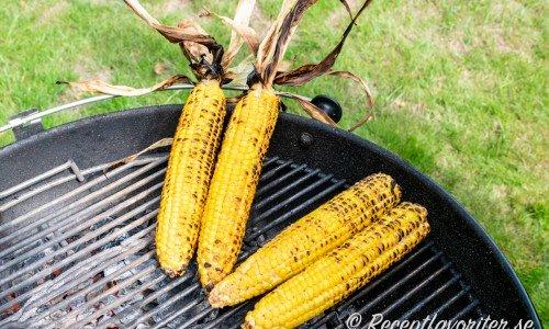 Färska majskolvar som grillas för att få färg med blast som handtag eller utan blast.