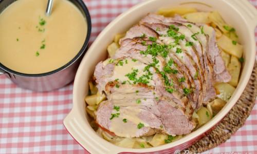 Helstekt karré eller kotlett med sås från stekskyn samt rotgrönsaker som vitkål som fått steka med köttet.