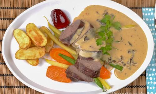 Helstekt rensadel - ovan skivad med gräddig trattkantarellsås; kokt morot, vaxbönor och gröna bönor samt rostade potatisar och en gelé med röda vinbär.