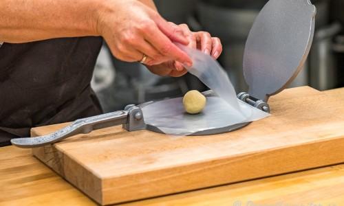 Majsdegen formas till bollar och pressa mellan lite tjock plast till tortillas