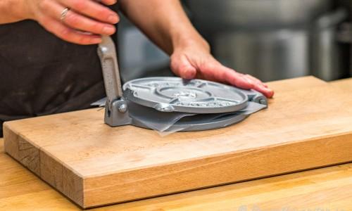Degen pressas till en tortilla i tortillapressen