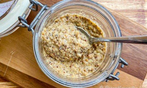 Hemlagad senap med gula och bruna senapsfrön i glasburk.