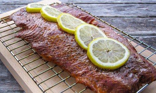 Servera den rökta laxen eller fisken med citronskivor och lägg över på en skärbräda eller fat.