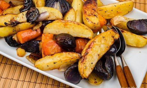 Honungsrostad potatis med morot, rödlök, vitlök, timjan och olivolja på serveringsfat.