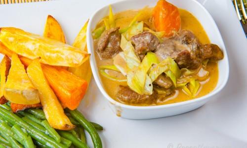 Höstgryta med kött och grädde serverad i skål på tallrik med tillbehör