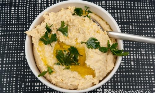 Hummus i skål med olivolja och persilja