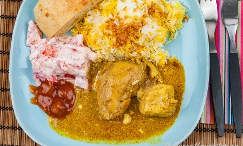 Indisk currygryta med kycklingdelar på tallrik med tillbehör