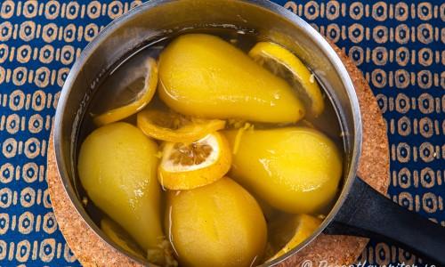 Päronen i sockerlag med ingefära, citron och vanilj i en kastrull.