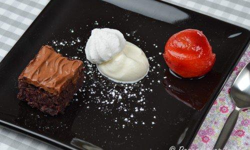 Ett inkokt plommon serveras som tillbehör till en rödbets- och chokladkaka, en klick vispad grädde samt maräng garnerat med lite florsocker.