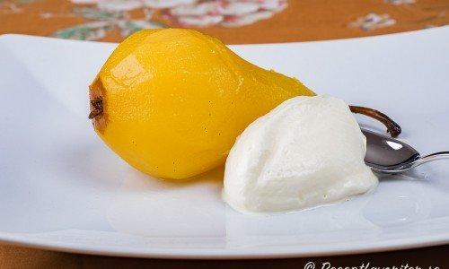 Ett päron serverat med en klick vispad grädde - enkelt och gott som dessert.