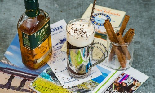 Irish coffee serverat i glas toppad med vispad grädde