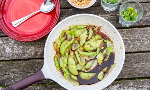 Ärtorna smaksätts i stekpanna eller wok med sojamarinaden och toppas med jordnötter och färsk koriander.