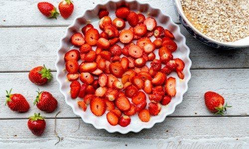 Sköljda och skivade jordgubbar i botten på pajform till pajen.